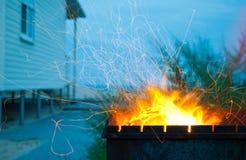 O fogo alaranjado acende o soldador metálico na casa do fundo do céu azul no litoral Fotos de Stock