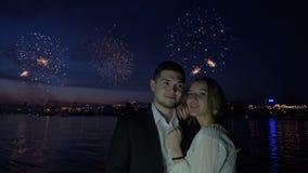 O fogo de artifício e os amantes novos estão abraçando na noite video estoque