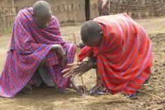 O fogo de fatura masculino do Masai friccionando cola junto na vila perto do parque nacional de Tsavo, Kenya, África foto de stock royalty free