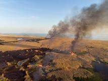 O fogo destrói os campos de juncos secos ao longo da costa do mar Opinião do olho do ` s do pássaro imagem de stock