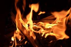 O fogo na lareira em um fundo preto, a chama incandesce, fotografia de stock