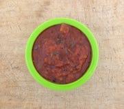 O fogo roasted esmagou tomates em uma bacia verde Fotografia de Stock Royalty Free