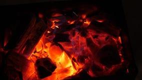 O fogo vermelho queima a madeira na obscuridade, cinza no fogo, close up carvões quentes para o soldador foto de stock