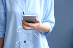 O fone de ouvido do desgaste de mulher com utilização do smartphone para escuta música Fotografia de Stock