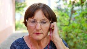O fones de ouvido vermelho idoso do desgaste de mulher e escuta a música filme