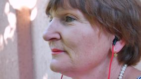 O fones de ouvido vermelho superior do desgaste de mulher adulta e escuta a música video estoque