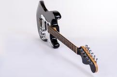 O formulário clássico da guitarra elétrica preto e branco é uma borda com o pescoço de madeira do bordo Imagens de Stock