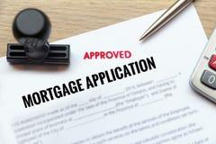 O formulário de candidatura aprovado da hipoteca estabelece na mesa de madeira com Foto de Stock