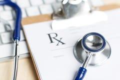 O formulário da prescrição grampeou para acolchoar o encontro na tabela com o teclado Imagens de Stock