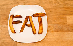 O forno cozeu microplaquetas de batata em um FAT de soletração da placa branca Foto de Stock