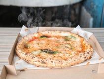 O forno italiano saboroso cozeu a pizza na caixa da entrega fotografia de stock