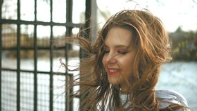 O forte vento funde o cabelo vermelho de uma senhora bonita Suportes da menina nas madeiras e na lagoa vídeos de arquivo