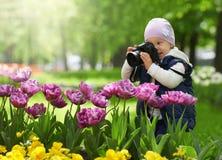 O fotógrafo amador pequeno é feliz e surpreendido pela qualidade tomar a imagem com a ajuda da câmera profissional