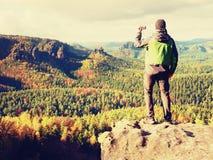 O fotógrafo amador prepara a câmera toma fotos impressionantes de montanhas enevoadas da queda imagem de stock