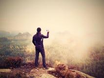 O fotógrafo amador prepara a câmera toma fotos impressionantes de montanhas enevoadas da queda imagem de stock royalty free