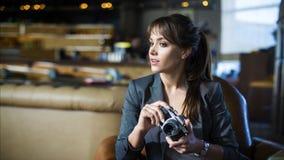 O fotógrafo bonito da menina está guardando a câmera em suas mãos Jovem mulher que olha o visor e que faz a foto no café Foto de Stock
