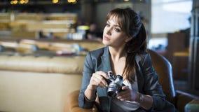 O fotógrafo bonito da menina está guardando a câmera em suas mãos Jovem mulher que olha o visor e que faz a foto no café Fotografia de Stock