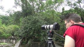 O fotógrafo caucasiano toma imagens com câmera de DSLR filme