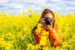 O fotógrafo da jovem mulher com um DSLR, vestindo um revestimento alaranjado, toma uma imagem em um campo da colza, campo rural,  fotos de stock royalty free