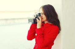 O fotógrafo da jovem mulher toma a imagem na câmera do vintage na cidade do inverno Foto de Stock Royalty Free