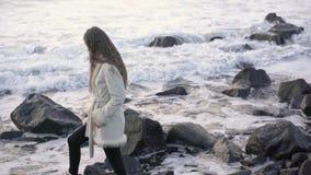 O fotógrafo da menina na costa do mar tormentoso faz imagens Fotógrafo do viajante do turista que faz o oceano das imagens vídeos de arquivo