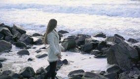 O fotógrafo da menina na costa do mar tormentoso faz imagens Fotógrafo do viajante do turista que faz o oceano das imagens filme