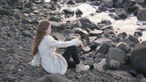 O fotógrafo da menina na costa do mar tormentoso faz imagens Fotógrafo do viajante do turista que faz o oceano das imagens video estoque