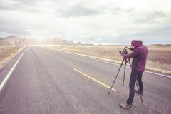 O fotógrafo da paisagem toma imagens em uma estrada vazia Fotografia de Stock