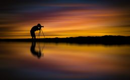 O fotógrafo da silhueta toma a foto o seascape bonito no por do sol imagens de stock royalty free