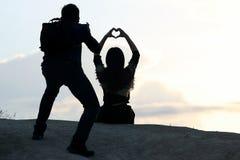 O fotógrafo dispara em uma menina com mãos sob a forma de um aga do coração Imagem de Stock Royalty Free