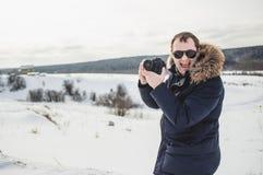 O fotógrafo do caminhante aprecia um panorama fino da floresta do inverno no dia ensolarado Foto de Stock
