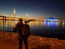 O fotógrafo está preparando-se para disparar em vistas a Lakhta O Golfo da Finl?ndia iluminou por luzes multi-coloridas na noite fotografia de stock royalty free