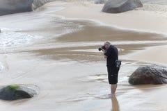 O fotógrafo está tomando uma imagem na praia fotografia de stock royalty free
