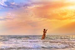 O fotógrafo fêmea com a câmera profissional que está no mar e toma a imagem do por do sol Fêmea no vestido nas ondas Fotos de Stock Royalty Free