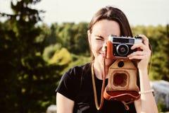 O fotógrafo fêmea feliz novo anda no parque com câmera retro Fotos de Stock