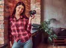 O fotógrafo feliz da moça vestiu-se em uma camisa e nas calças de brim de manta que guardam uma câmera e que olham a câmera ao in fotografia de stock