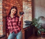 O fotógrafo feliz da moça vestiu-se em uma camisa e nas calças de brim de manta que guardam uma câmera e que olham a câmera ao in imagem de stock
