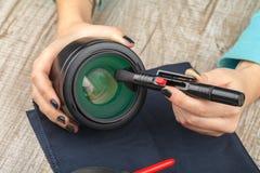 O fotógrafo limpa a lente da lente da poeira imagens de stock