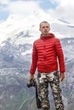 O fotógrafo masculino com a câmera nas mãos está em um fundo de Fotografia de Stock Royalty Free