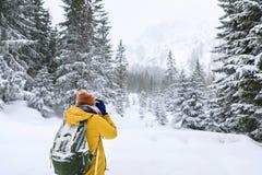 O fotógrafo na floresta do inverno fotografia de stock