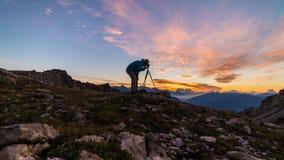 O fotógrafo na parte superior da montanha com a câmera no tripé em scenis coloridos do céu da luz do nascer do sol ajardina, conq foto de stock