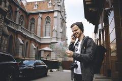 O fotógrafo novo que gosta de viajar está verificando seu lugar atual durante o telefonema fotografia de stock