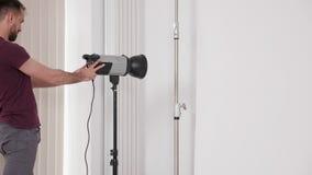 O fotógrafo profissional da forma aumenta as luzes e os poderes instantâneos ele acima video estoque