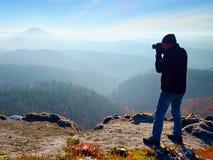 O fotógrafo profissional toma fotos com a câmera do espelho no pico da rocha Névoa sonhadora Imagens de Stock