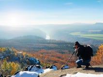 O fotógrafo profissional toma fotos com câmera e tripé do espelho no pico nevado Foto de Stock