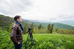 O fotógrafo profissional toma fotos com a câmera no pico da rocha Imagens de Stock