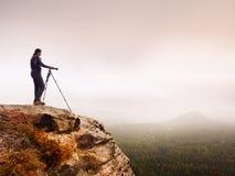 O fotógrafo profissional toma fotos da paisagem enevoada com câmera e tripé do espelho Fotos de Stock