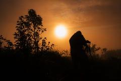 O fotógrafo toma a fotos os primeiros raios do sol de aumentação fotos de stock royalty free