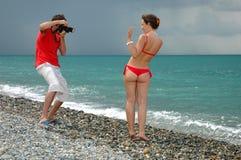 O fotógrafo toma a retratos um modelo no biquini Fotos de Stock Royalty Free
