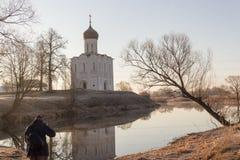 O fotógrafo toma uma paisagem bonita da igreja no lago no nascer do sol Imagem de Stock